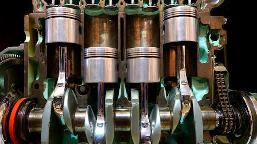 actual image of car engine showing four piston cylinder and crank shaft